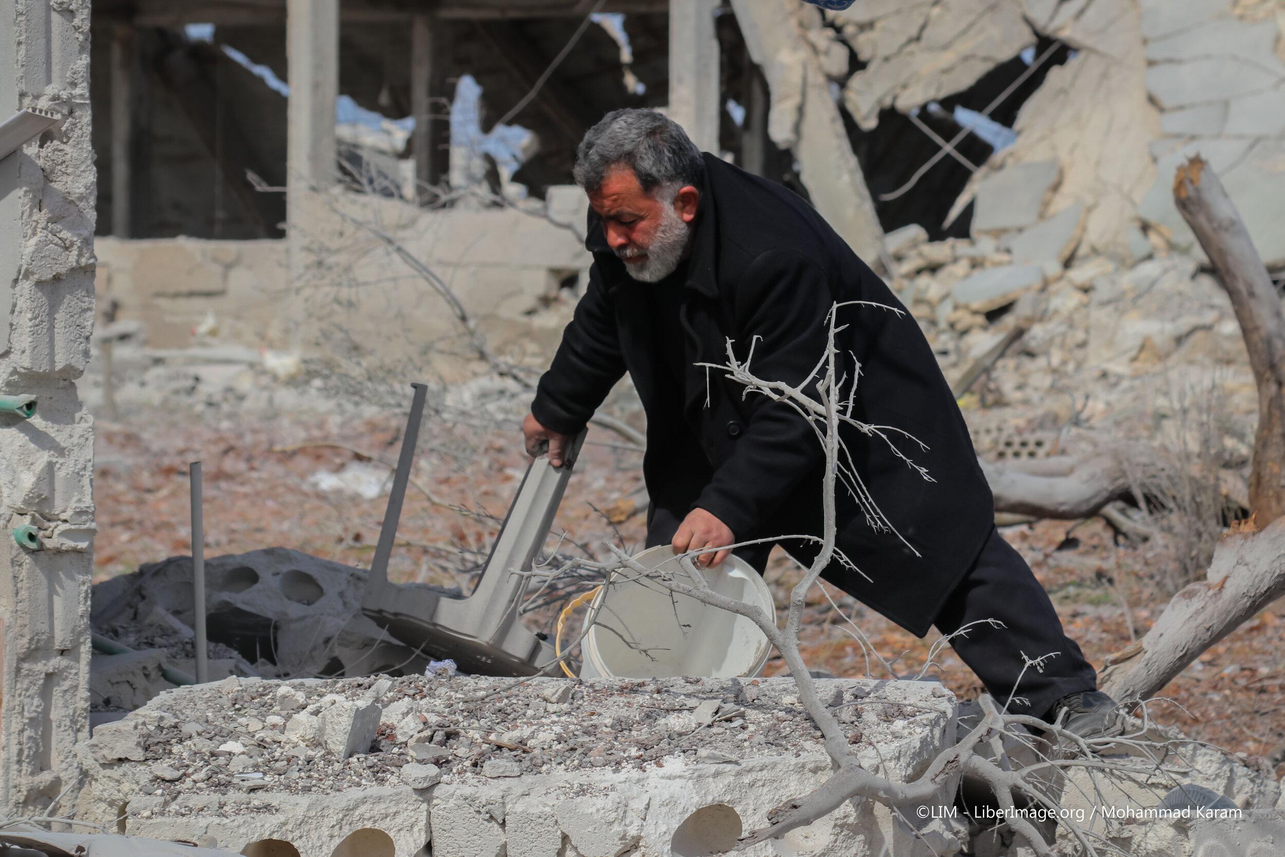 رجل سوري يبحث في أنقاض بيته بعد قصف طائرات النظام